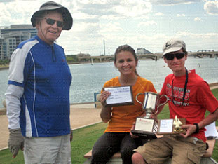 High School coach George Tingom presents winning trophies to Madison Cordova and Cedric Lorch.